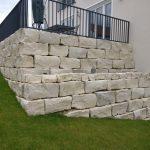 Eine fertige Terrasse mit Hangsicherung aus Jura-Blöcken